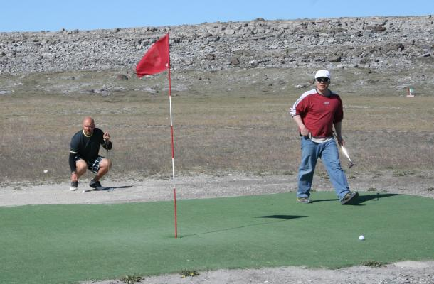 Two golfers on the green at the Billy Joss Open Golf Tournament.